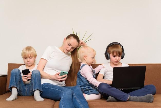 Moeder en drie kinderen zitten op de bank met elk een eigen gadget. probleem van het moderne generatieconcept.