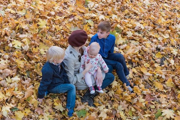 Moeder en drie kinderen zitten op gevallen bladeren in de herfstbos