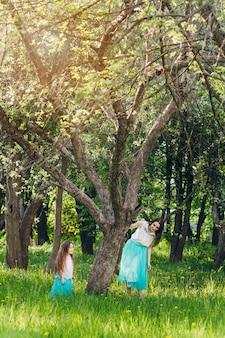 Moeder en een kleine dochter lopen in de lente bloeiende apple