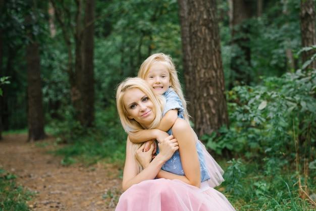 Moeder en een vijfjarige dochter in identieke roze tule rokken en blauwe spijkeroverhemden lopen in het park of in het bos.