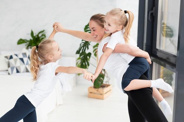 Moeder en gelukkige dochter die thuis spelen