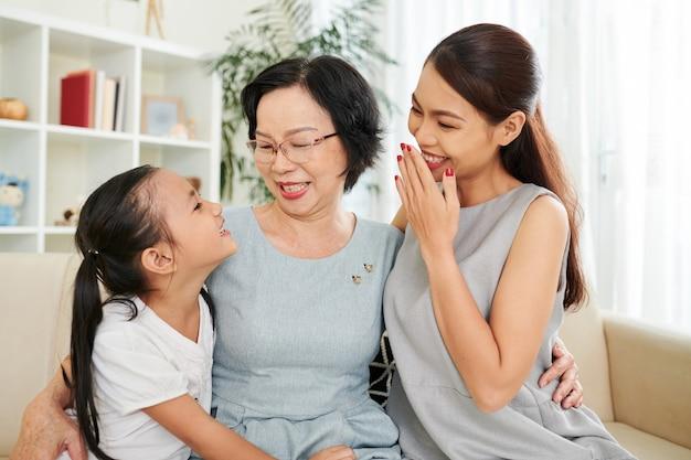 Moeder en grootmoeder lachen om grappige grap van preteen klein meisje, ze knuffelen en zitten thuis op de bank