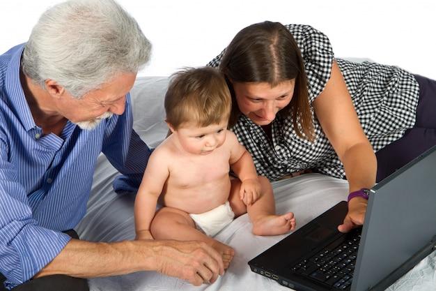 Moeder en grootvader met baby spelen met pc