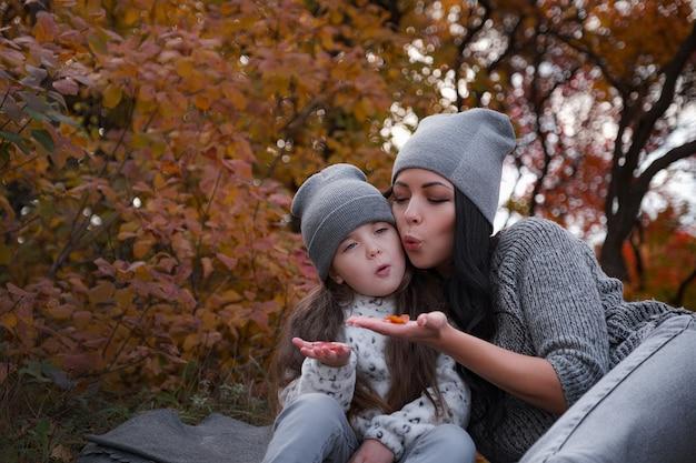 Moeder en haar 4-jarige dochter brengen weekend door, picknicken samen in het herfstbos. moeder en kind relaties.