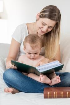 Moeder en haar 9 maanden oude babyjongen zitten op de bank en lezen een groot boek