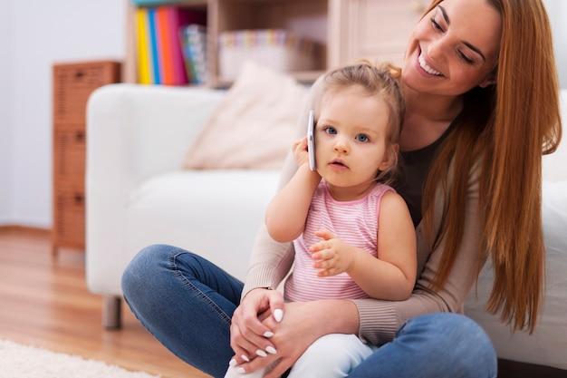 Moeder en haar baby met behulp van mobiele telefoon thuis