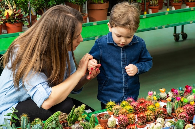 Moeder en haar babyjongen die in een plantenwinkel cactussen bekijken. tuinieren in serre. botanische tuin, bloementeelt, tuinbouwconcept