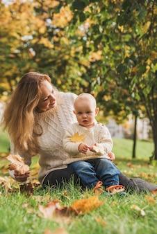 Moeder en haar babyjongen, genieten van de herfstdag in park.