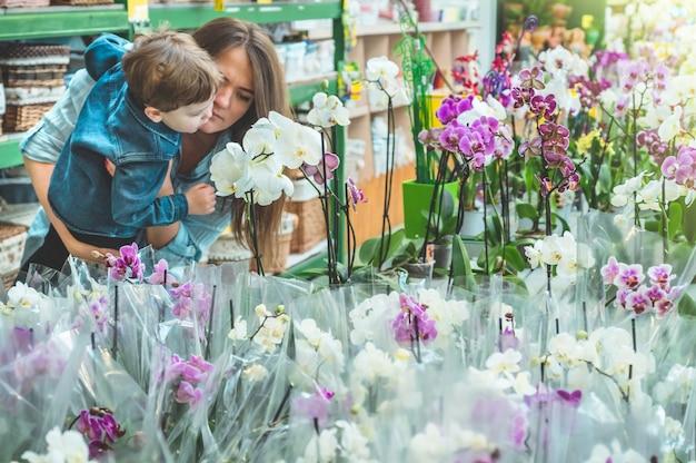 Moeder en haar babyjongen klant ruiken kleurrijke bloeiende orchideeën in de winkel. tuinieren in serre. botanische tuin, bloementeelt, tuinbouwconcept