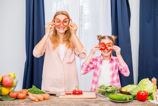 Moeder en haar dochter die rode groene paprika voor hun huis houden