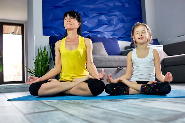 Moeder en haar dochter die yoga samen thuis doen.