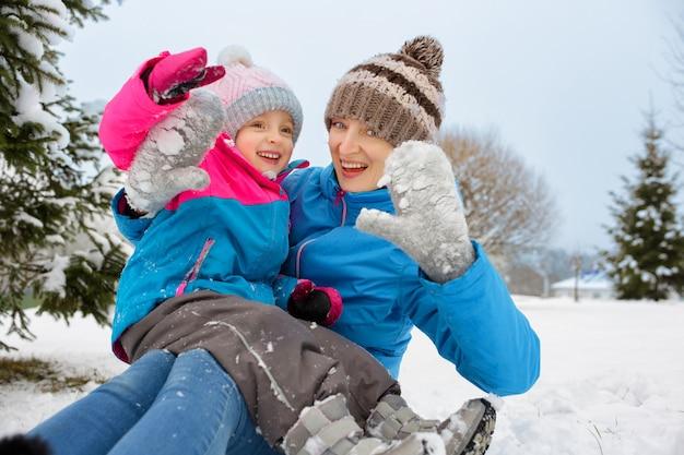Moeder en haar dochter hebben plezier met spelen in de sneeuw in de winter, positief gelach en gelach