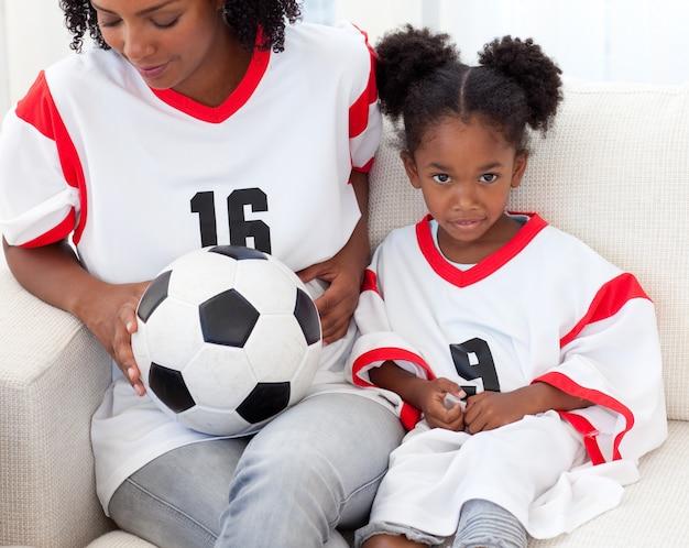 Moeder en haar dochter kijken naar een voetbalwedstrijd