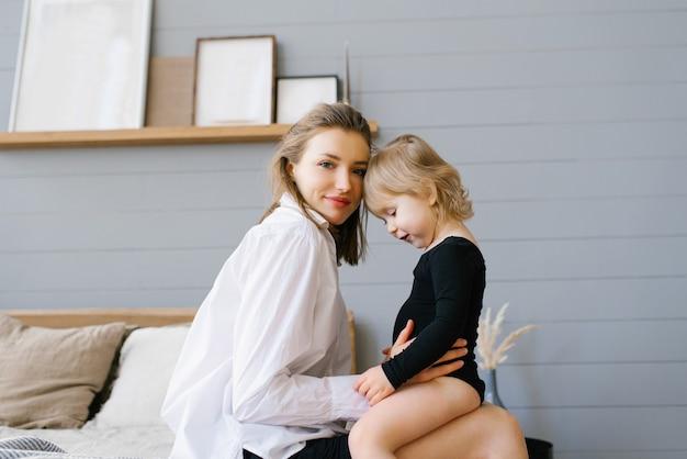 Moeder en haar dochter knuffelen samen terwijl ze op bed zitten