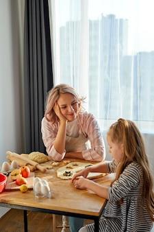 Moeder en haar dochter koken in de keuken tot moederdag. praat en geniet van het proces. lifestyle fotoserie in licht interieur, in een lichte kamer