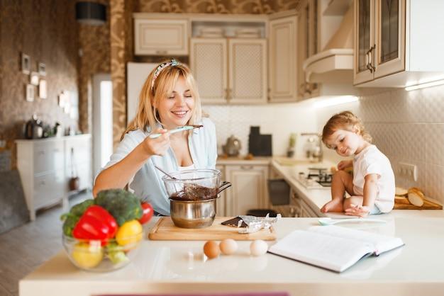 Moeder en haar dochter proeven gesmolten chocolade