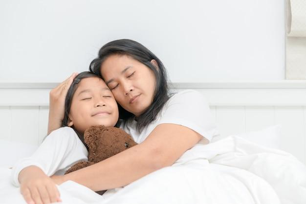 Moeder en haar dochter slapen samen op bed,