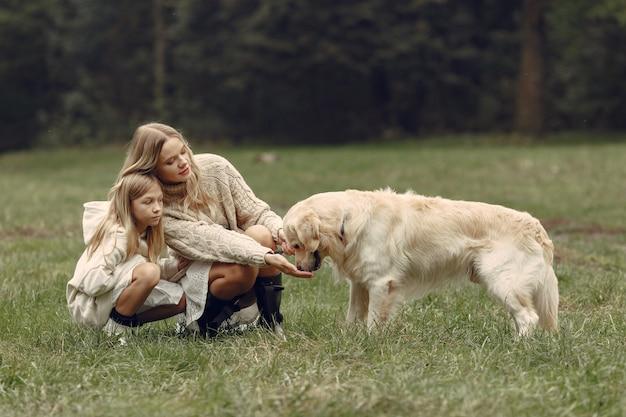 Moeder en haar dochter spelen met hond. familie in de herfstpark. huisdier, huisdier en levensstijl concept