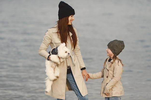 Moeder en haar dochter spelen met hond. huisdier, huisdier en levensstijl concept