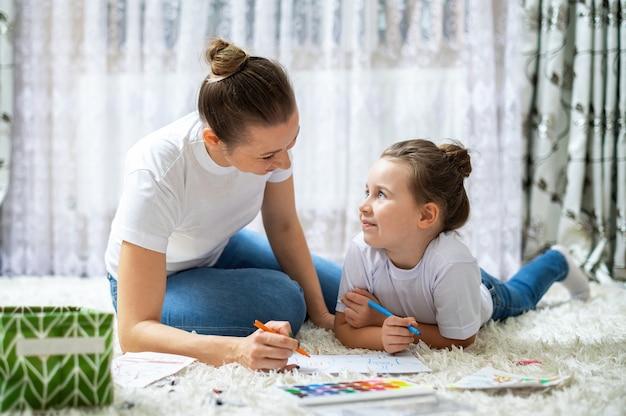 Moeder en haar dochter spelen thuis samen op de vloer. blij en lachend