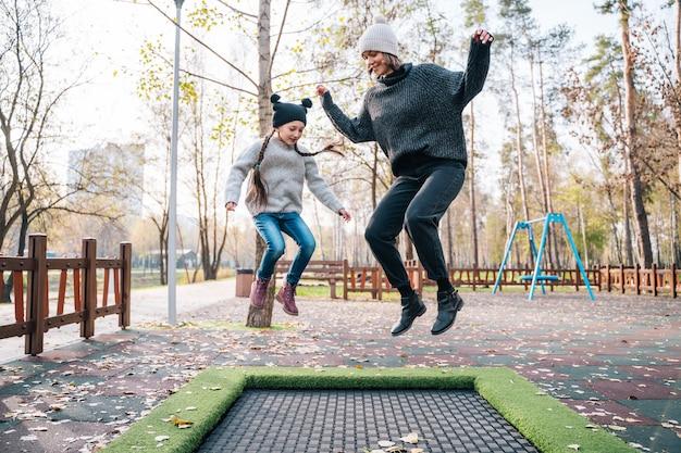 Moeder en haar dochter springen samen op trampoline in herfst park