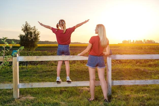 Moeder en haar dochter staan met gestrekte armen op de rug bij zonsondergang