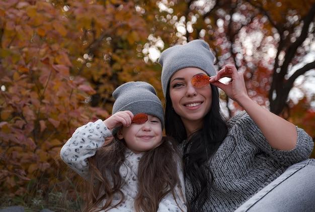 Moeder en haar dochter van 4 jaar brengen weekend door, picknicken samen in het herfstbos