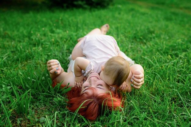 Moeder en haar dochter van één jaar knuffelen op het gras in het park.