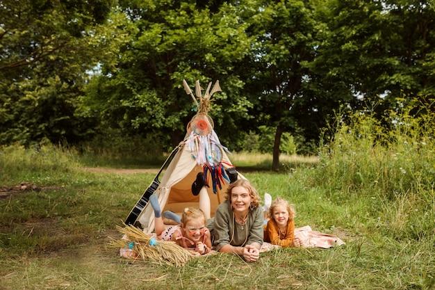 Moeder en haar dochters brengen in de zomer tijd buiten door in het bos, naast wigwam, tipi-decoratie.
