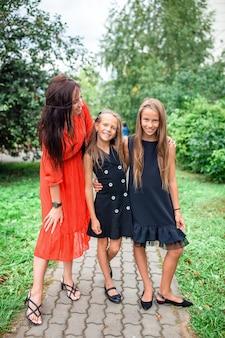 Moeder en haar dochters naar school. schattige kleine meisjes voelen zich erg opgewonden om terug naar school te gaan