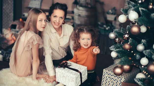 Moeder en haar dochters openen een geschenkdoos bij de kerstboom. vakantie concept
