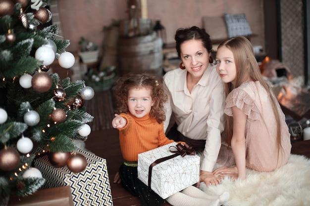 Moeder en haar dochters openen een geschenkdoos in de buurt van de kerstboom.