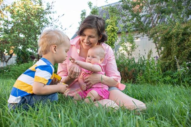 Moeder en haar dochtertje en zoon lachen en hebben plezier in de tuin, gelukkig gezin
