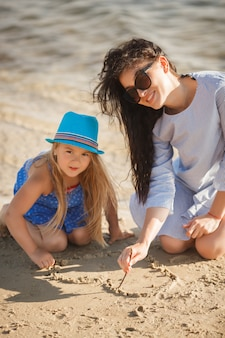 Moeder en haar dochtertje hebben plezier aan de kust. jonge mooie moeder en haar kind spelen in de buurt van het water en hart puttend uit het zand