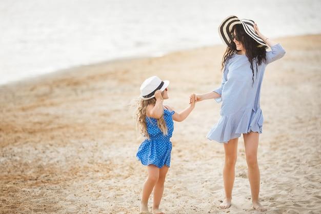 Moeder en haar dochtertje hebben plezier aan de kust. jonge mooie moeder en haar kind spelen in de buurt van het water