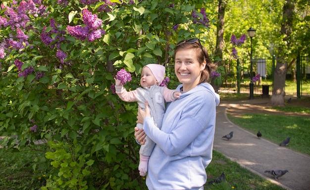 Moeder en haar dochtertje lachen en hebben plezier buiten in de tuin buiten gelukkig gezin