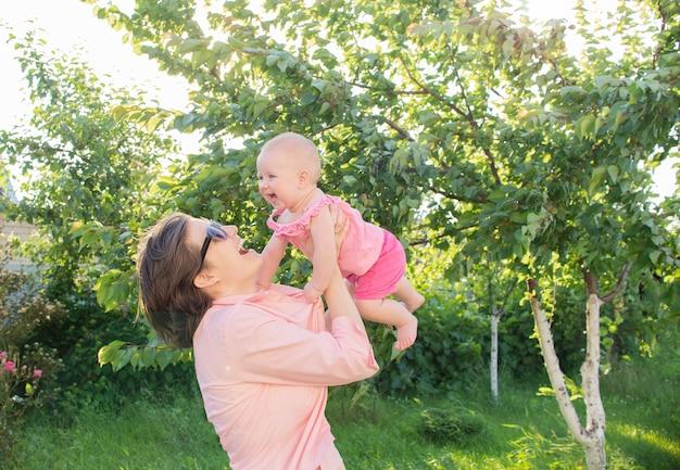 Moeder en haar dochtertje lachen en hebben plezier buiten in de tuin buiten.