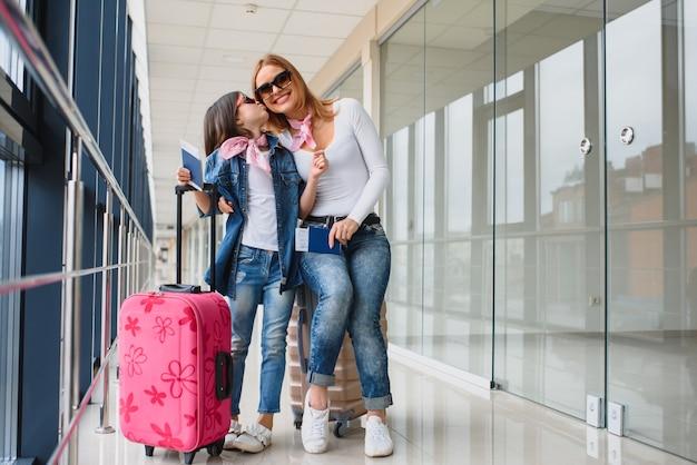 Moeder en haar dochtertje met bagage op de luchthaven