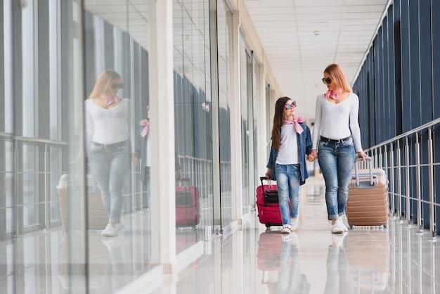 Moeder en haar dochtertje met bagage op de luchthaven Premium Foto