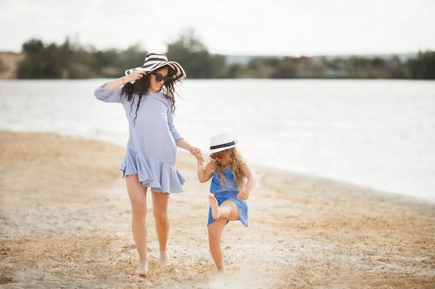 Moeder en haar dochtertje plezier aan de kust. jonge mooie moeder en haar kind spelen in de buurt van het water