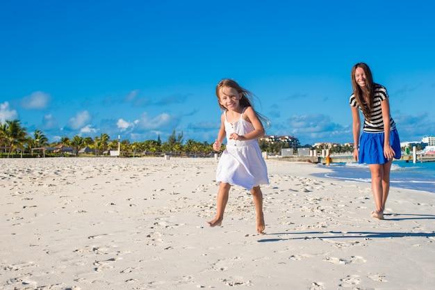 Moeder en haar dochtertje plezier op exotische strand op zonnige dag