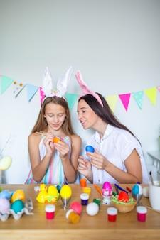 Moeder en haar dochtertje schilderen eieren en gelukkige familie pasen voorbereiden