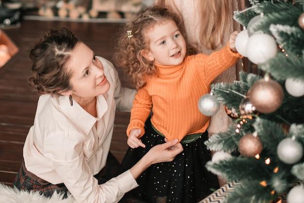 Moeder en haar dochtertjes versieren de kerstboom. vakantie concept