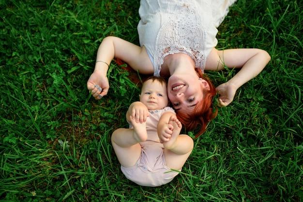 Moeder en haar eenjarige dochter liggen op het gras in het park.