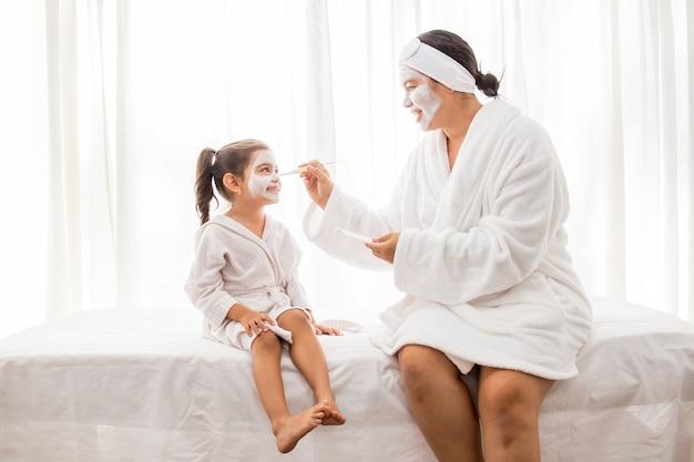 Moeder en haar jonge mooie dochter hebben plezier in de slaapkamer en maken gezichtsmaskers van klei
