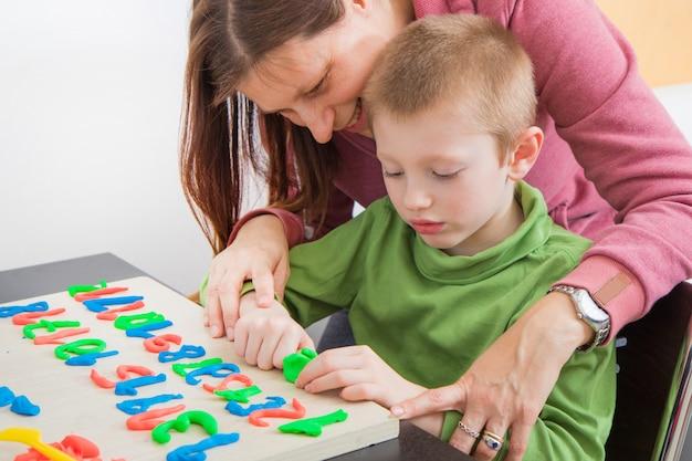 Moeder en haar jongen spelen met gekleurde boetseerklei tijdens de quarantaine van het coronavirus