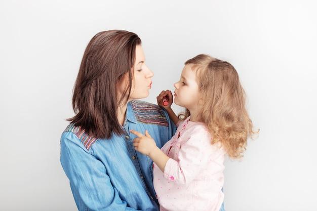 Moeder en haar kind dochter meisje met een lippenstift