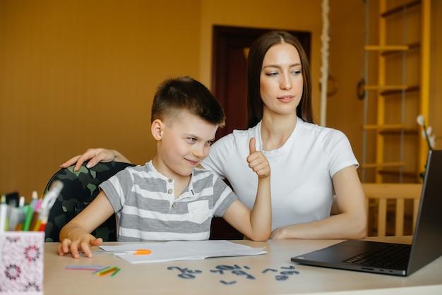 Moeder en haar kind zijn thuis bezig met afstandsonderwijs voor de computer.