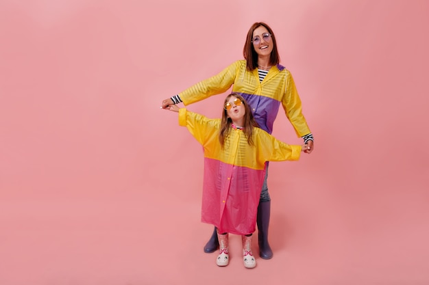 Moeder en haar kinddochtermeisje die heldere regenjassen dragen. mooie jonge vrouw met haar dochter en glimlacht