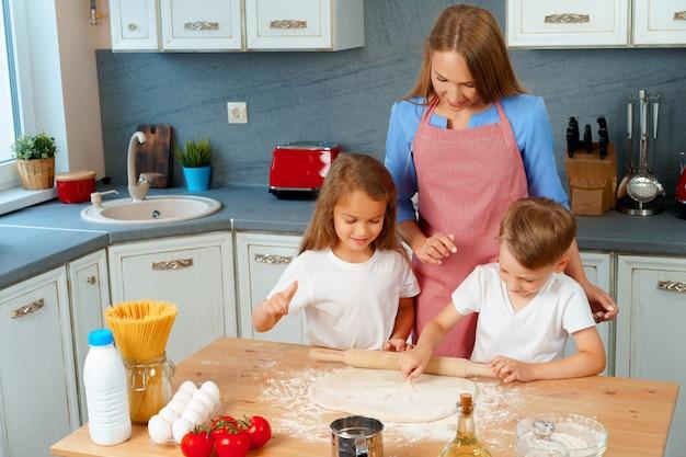 Moeder en haar kinderen die deeg in keuken koken